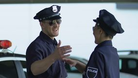 Smiling police colleagues giving high-five, patrol together, security confidence. Stock footage stock video footage