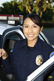 Smiling police officer. A Hispanic police officer standing and smiling next to her patrol car Royalty Free Stock Photography