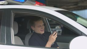 Smiling policeman in patrol car chatting on smartphone, social network addiction. Stock footage stock footage