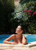 Smiling pool. Female in pool smiling with flowers in background royalty free stock photography