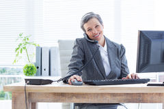 Smiling portrait businesswoman phoning and using computer Royalty Free Stock Photography