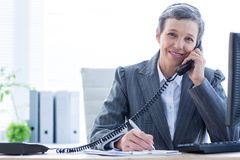 Smiling portrait of a businesswoman phoning and writing Stock Photos