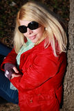 Smiling portrait of a caucasian woman with red jacket and sunglasses Stock Photo