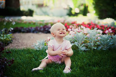 Smiling portrait cute baby-girl on green grass Royalty Free Stock Photos