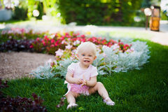 Smiling portrait cute baby-girl on green grass Royalty Free Stock Photo