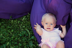 Smiling portrait cute baby-girl on green grass Royalty Free Stock Image