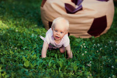 Smiling portrait cute baby-girl on green grass Stock Image