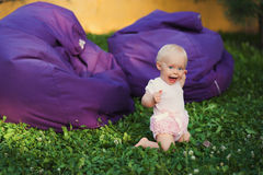 Smiling portrait cute baby-girl on green grass Stock Images