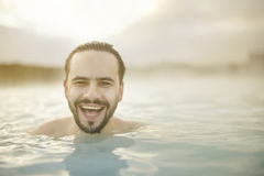 Smiling portrait in pool. Sunny portrait of smiling young man in the pool of Blue Lagoon in Iceland stock photography