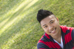 Smiling portrait of a young man. A close up shot of a smiling young man, with grass in the background Royalty Free Stock Images