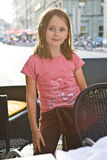 Smiling Posing Girl Child City Street. A young girl in a pink t-shirt with floral motif strikes a pose amidst restaurant chairs outdoors with a street and stock image