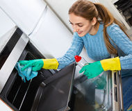Smiling positive adult girl removing snuff in oven Stock Photos