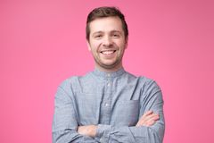 Smiling positive caucasian man in blue shirt. Attractive handsome smiling positive caucasian man in blue shirt on pink background. Studio shoot royalty free stock image