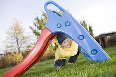 Smiling positive child sit under slide on grass Royalty Free Stock Images