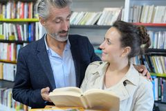 Smiling positive couple taking chosen books in book shop royalty free stock photo