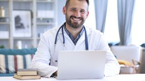 Smiling positive doctor at work looking at camera