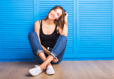 Smiling positive emotional woman sitting against blue background. Royalty Free Stock Photography