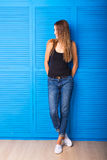 Smiling positive emotional woman standing against blue background. Royalty Free Stock Images