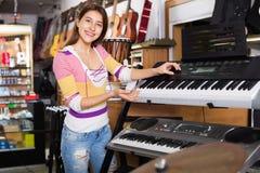 Smiling positive  girl choosing synthesizer Stock Photos