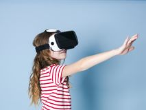 Smiling positive girl wearing virtual reality glasses goggles headset, vr box. connection, modern, new generation, concept. Girl trying to touch objects in royalty free stock images