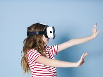 Smiling positive girl wearing virtual reality glasses goggles headset, vr box. connection, modern, new generation, concept. Girl trying to touch objects in stock photo