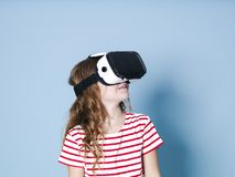 Smiling positive girl wearing virtual reality glasses goggles headset, vr box. connection, modern, new generation, concept. Girl trying to touch objects in royalty free stock image