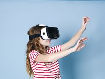 Smiling positive girl wearing virtual reality glasses goggles headset, vr box. connection, modern, new generation, concept. Girl trying to touch objects in stock photography