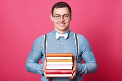 Smiling positive man holds bunch of colorful books in both hands, posing isolated over pink background in studio. Athletic strong. Man wears blue shirt, stylish royalty free stock image