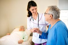 Smiling positive nurse worries about senior patients. At nursing home Royalty Free Stock Images