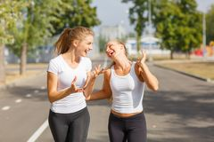 Smiling, positive, pretty girls running on a park background. Sports with friends concept. Royalty Free Stock Photos