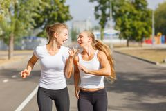 Smiling, positive, pretty girls running on a park background. Sports with friends concept. Royalty Free Stock Images
