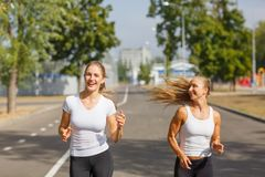Smiling, positive, pretty girls running on a park background. Sports with friends concept. Stock Image