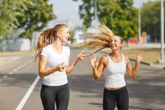 Smiling, positive, pretty girls running on a park background. Sports with friends concept. Royalty Free Stock Photography