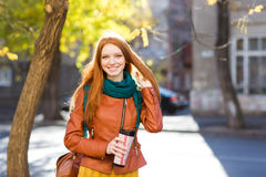 Smiling  positive woman holding tumbler of coffee Stock Photos