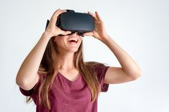 Smiling positive woman wearing virtual reality goggles headset, vr box. Connection, technology, new generation, progress concept. Girl trying to touch objects stock images