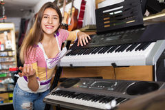 Smiling positive young girl choosing synthesizer Royalty Free Stock Photography