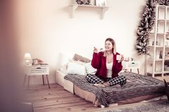 Smiling positive young lady spending coffee break in bedroom royalty free stock photography