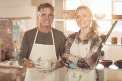 Smiling potters standing in pottery shop Royalty Free Stock Image