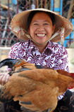 Smiling Poultry Vendor, Hoi An, Vietnam. A happy vendor offers a live chicken for sale in the markets of Hoi An in central Vietnam Royalty Free Stock Image