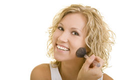 Smiling while powdering. Blonde woman is using powder on her face stock photos