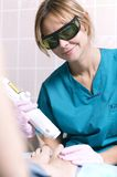Smiling practitioner doing a laser treatment Stock Photography