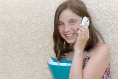 Smiling pre teenager girl calling on smartphone, outdoor Royalty Free Stock Images