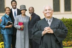 Smiling Preacher in church garden worshipers in background portrait Stock Image