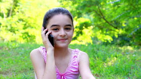 Smiling preeteen girl talking on smart phone stock video footage