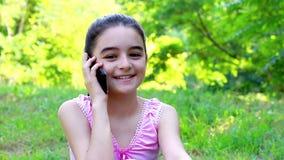 Smiling preeteen girl talking on smart phone stock video footage