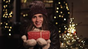 Smiling Preety Girl in Winter Hat and Mittens Holding a red Present Box. Woman Looking Happy, Standing at Lights and stock video footage