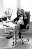 Smiling pregnant businesswoman talking on phone at working place Royalty Free Stock Images
