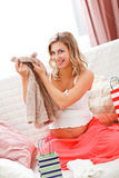 Smiling pregnant examines purchases for baby Royalty Free Stock Photography