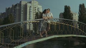Smiling couple in love embracing on the bridge. Smiling pregnant family standing on pedestrian bridge and looking at view over urbanscape background. Romantic stock video footage