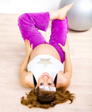 Smiling pregnant female doing fitness exercises Royalty Free Stock Images
